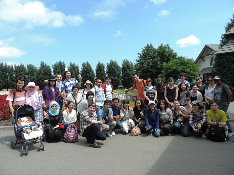 HUISA Summer Trip participants, consisted by Hokkaido University students, staff, and their familiy and friends, pose for a group photo at Farm Tomita, Furano.